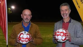 Two men holding soccer balls